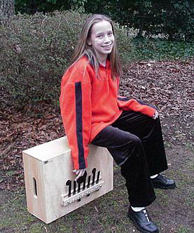 Photo of girl sitting on a bassbox and playing it